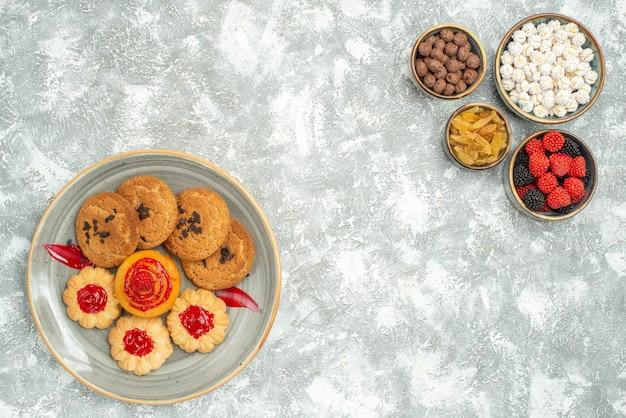 上面図白い背景の上の甘いビスケットとキャンディーとおいしい砂のクッキーケーキクッキースウィートティーティー