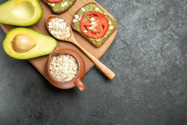 Вид сверху вкусные бутерброды с авокадо и красными помидорами на сером фоне обед закуска бургер сэндвич