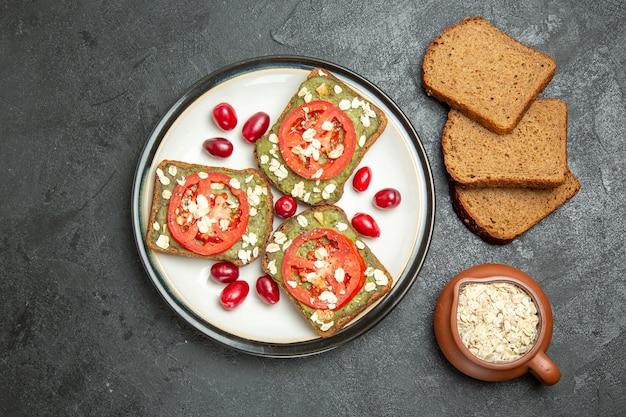 灰色の表面のハンバーガーサンドイッチパンスナックパンのプレートの内側にアボカドパスタとトマトが入ったトップビューのおいしいサンドイッチ