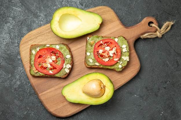 Top view delicious sandwiches with avocado and red tomatoes on a grey surface snack meal burger sandwich bread