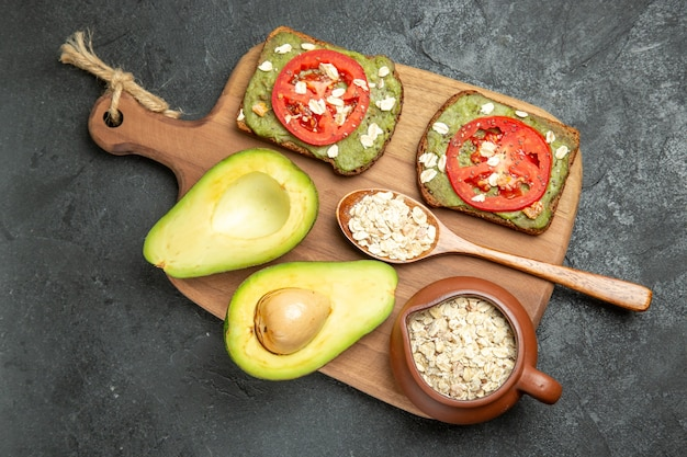 Top view delicious sandwiches with avocado and red tomatoes on the grey surface snack meal burger sandwich bread