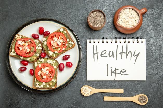 スライスしたトマトと健康的な生活が灰色の背景に書いている上面図おいしいサンドイッチスナックパンハンバーガーサンドイッチパン