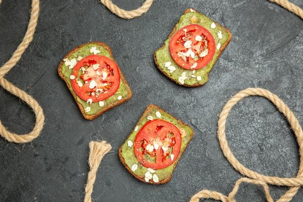 어두운 회색 표면 빵 버거 샌드위치 식사 간식에 고추 냉이와 빨간 토마토가 들어간 상위 뷰 맛있는 샌드위치