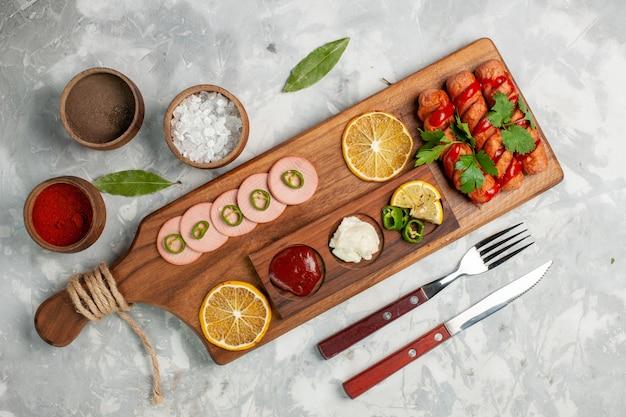 Вид сверху вкусные колбаски с лимоном и приправами на светло-белом столе, фрукты, овощи, еда