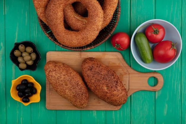 Vista dall'alto di deliziose polpette di sesamo su una tavola da cucina in legno con olive su una ciotola con verdure su una ciotola su un fondo di legno verde