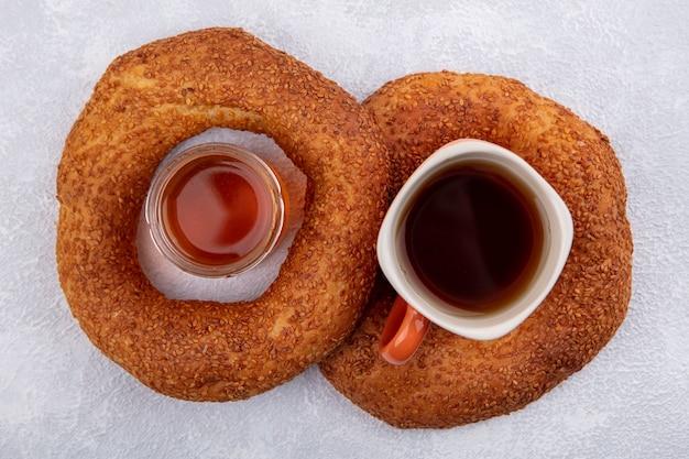 Vista dall'alto del delizioso bagel turco di sesamo con una tazza di tè e miele su uno sfondo bianco