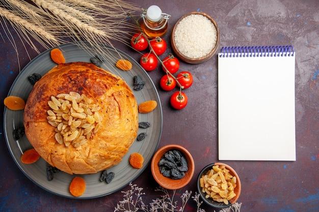 Vista dall'alto delizioso shakh plov cotto pasto di riso con uvetta e pomodori sull'impasto del pasto sfondo scuro cucinare la cena di riso