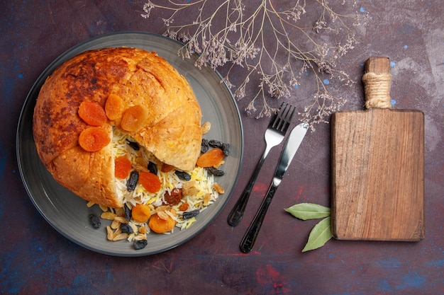 Top view of delicious shakh plov with raisins inside round dough on dark surface