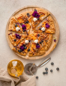 Top view of delicious slice of pizza with blueberries and flower petals