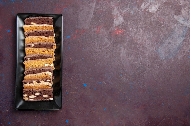 Top view delicious sliced cake with nuts inside cake pan on dark background sweet cocoa cake biscuit pie sugar cookie