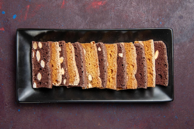 Top view delicious sliced cake with nuts inside cake pan on dark background sweet cocoa dough cake biscuit pie sugar