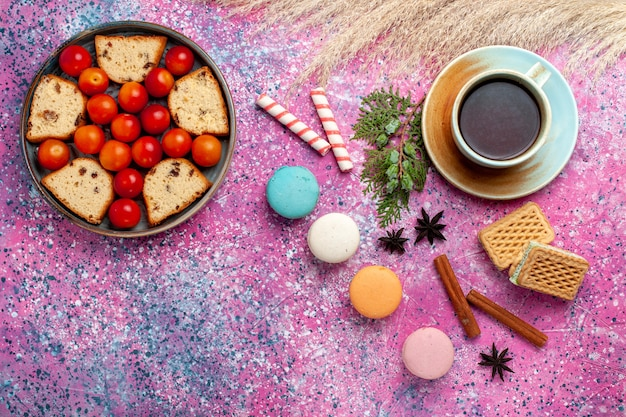 Вид сверху вкусный нарезанный торт с кислыми свежими сливами, французскими макаронами и чаем на розовом столе