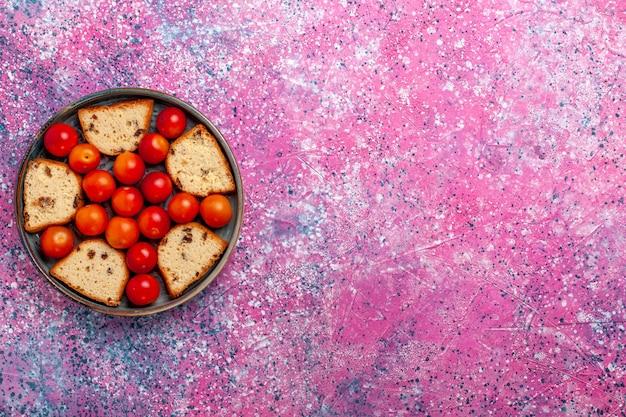 淡いピンクの表面に鍋の中に酸っぱい新鮮なプラムが入った上面図おいしいスライスケーキ