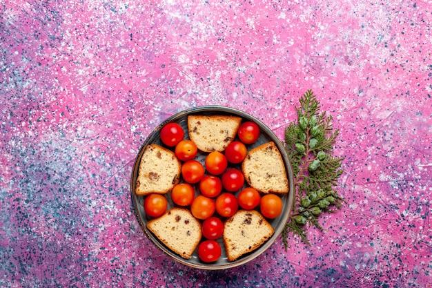 ピンクの表面の鍋の中に酸っぱい新鮮なプラムが入った上面図おいしいスライスケーキ