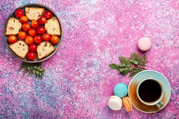 ピンクの机の上に酸っぱい新鮮なプラムマカロンとお茶とトップビューおいしいスライスケーキ