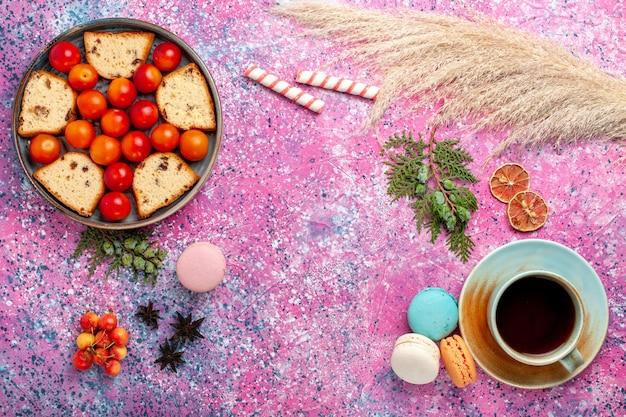 Vista dall'alto deliziosa torta a fette con macarons di prugne fresche acide e tè sulla superficie rosa