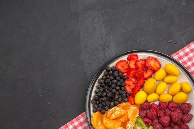 暗い写真のプレート内のおいしいスライスされた果物の上面図まろやかな果樹エキゾチックな熟した健康的な生活