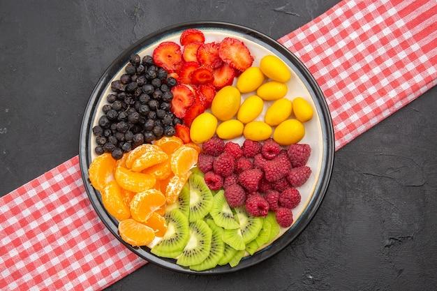 Вид сверху вкусных нарезанных фруктов внутри тарелки на темной фотографии спелых фруктовых деревьев экзотических спелых здоровых жизней