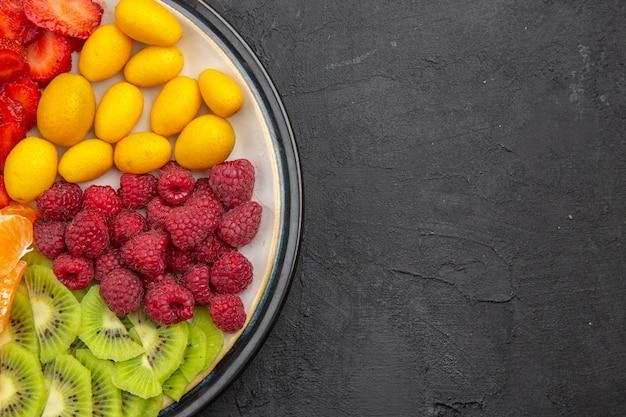 暗い熱帯果樹のプレート内のおいしいスライスされた果物の上面図エキゾチックな熟したダイエット写真無料のテキスト