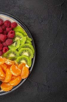 Вид сверху вкусные нарезанные фрукты внутри тарелки на темном фруктовом дереве экзотические спелые диеты фото тропические