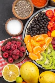 ダークフルーツの写真の新鮮な果物とプレート内のおいしいスライスされた果物の上面図まろやかな木熟した健康的な生活