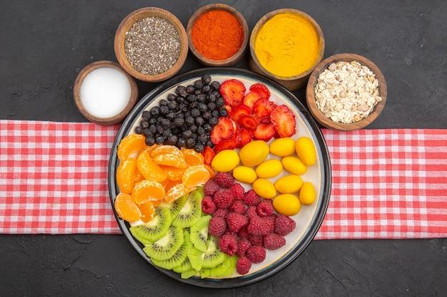 Vista dall'alto deliziosi frutti a fette all'interno del piatto con condimenti su una foto scura di un albero da frutto maturo esotica vita sana