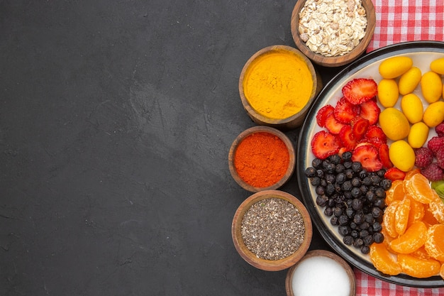 Вид сверху вкусные нарезанные фрукты внутри тарелки с приправами на темном фоне