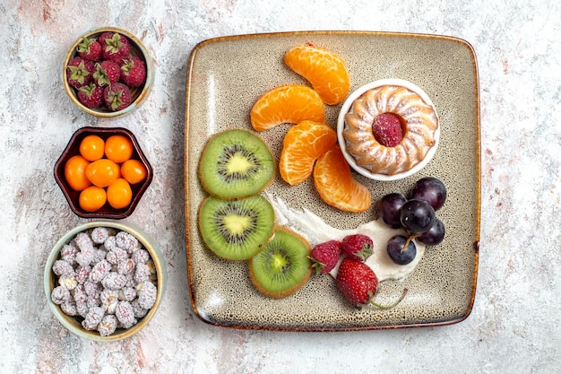 Top view delicious sliced fruits with cake and candies on white background fruit fresh tea candy cake biscuit