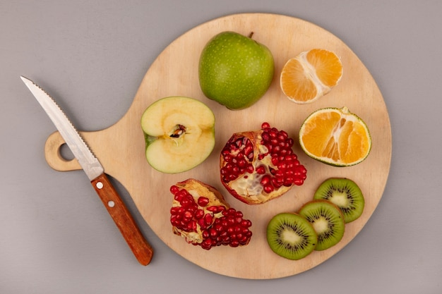 Vista dall'alto di deliziosi kiwi a fette con mela mandarino e melograno su una tavola da cucina in legno con coltello