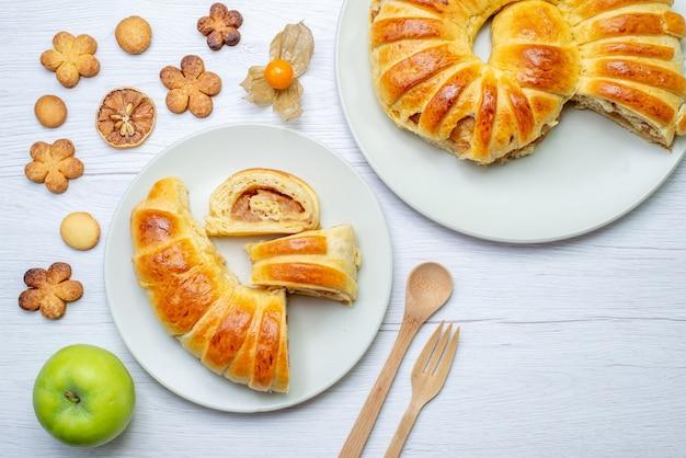 Vista dall'alto di deliziosi pasticcini affettati all'interno della piastra con ripieno insieme a forchetta di legno cucchiaio biscotti sulla scrivania bianca, pasticceria biscotto biscotto zucchero dolce
