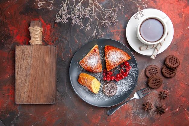 トップビューダークテーブルケーキの甘いパイティーにお茶を入れたおいしいスライスパイ