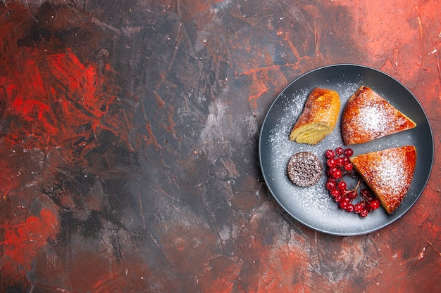 暗いテーブルのパイの甘いケーキに赤いベリーとおいしいスライスパイの上面図