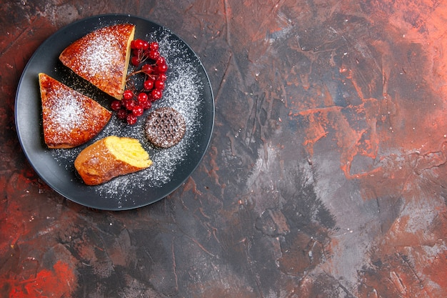 暗いテーブルの上の赤いベリーと甘いパイケーキの上面図おいしいスライスパイ