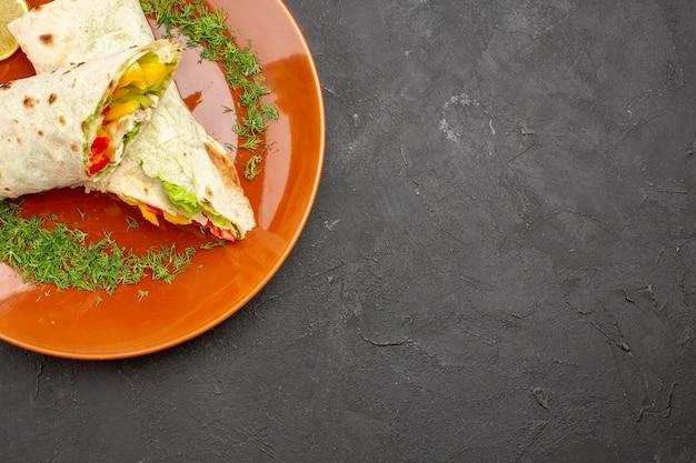 Vista dall'alto delizioso panino con insalata di shaurma affettato all'interno della piastra su sfondo scuro spuntino pasto hamburger pane sandwich