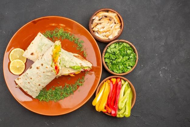 Вид сверху вкусный нарезанный сэндвич с салатом шаурма внутри тарелки на темном столе, сэндвич с гамбургером, закуска из хлеба