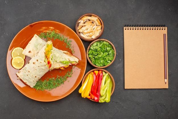 Vista dall'alto delizioso panino con insalata di shaurma affettato con verdure sullo sfondo scuro spuntino di panino con panino con hamburger Foto Gratuite