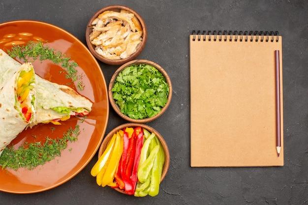 Vista dall'alto delizioso panino con insalata di shaurma affettato con verdure sullo sfondo scuro spuntino di panino con panino con hamburger