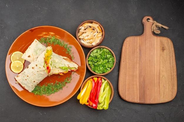 Vista dall'alto delizioso panino con insalata di shaurma affettato con verdure su spuntino di pane a sandwich con pasto di hamburger scuro da scrivania