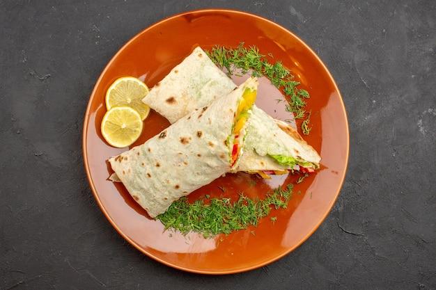 暗い背景のプレートの内側にレモンスライスが入ったおいしいスライスしたシャワルマサラダサンドイッチの上面図ハンバーガーミールスナックサンドイッチパン