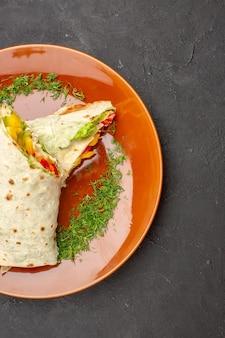 暗い背景のプレートの内側にレモンスライスが入ったおいしいスライスしたシャワルマサラダサンドイッチの上面図ハンバーガー食事スナックサンドイッチパン