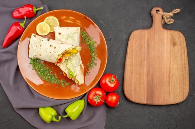 トップビュー暗い背景に新鮮な野菜とおいしいスライスしたシャワルマサンドイッチハンバーガーミールサンドイッチスナックパン