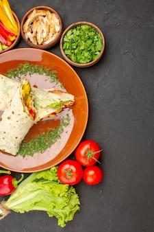 トップビュー暗い背景に野菜と緑のおいしいスライスしたシャワルマサンドイッチハンバーガーミールパンサンドイッチスナック