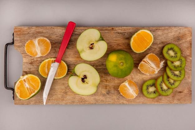Vista dall'alto di delizioso mandarino a fette con fette di kiwi e mela su una tavola di cucina in legno con coltello