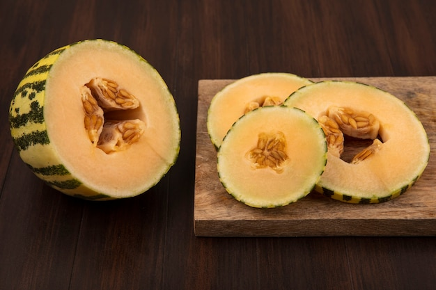 Top view of delicious slices of cantaloupe melon on a wooden kitchen board on a wooden wall