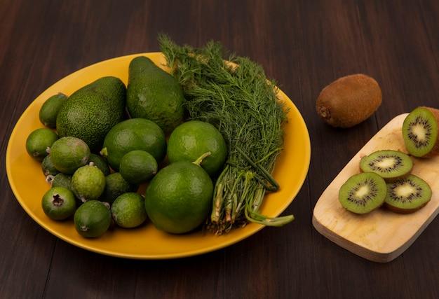 Vista dall'alto di deliziose fette di kiwi su una tavola da cucina in legno con avocado feijoas e limette su una piastra gialla su una parete in legno