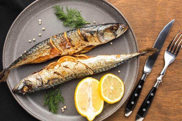 Вид сверху вкусной копченой рыбы на тарелке