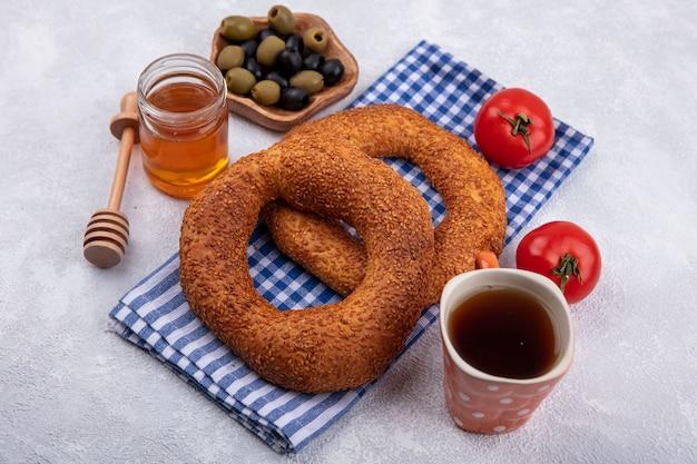 Vista dall'alto di deliziosi e morbidi bagel turchi tradizionali isolati su un panno controllato con pomodori e olive su una ciotola di legno con miele su un barattolo di vetro su sfondo bianco