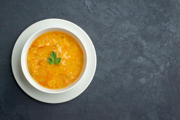 Вид сверху вкусного супа внутри белой тарелки на темной поверхности