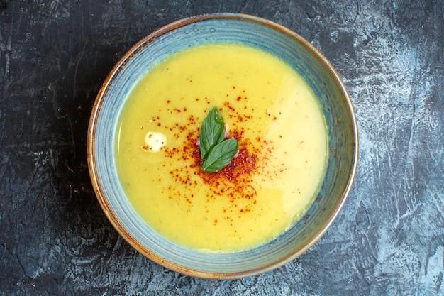 Vista dall'alto di una deliziosa zuppa servita con pepe e menta in una pentola blu su sfondo scuro