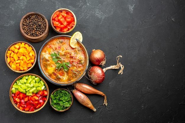 Вид сверху вкусного супа с зеленью и овощами на сером пространстве